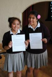 Krizette Garcia and Angelina Mesta hold up acceptance letters to NDNU received at On-Site Admissions Day